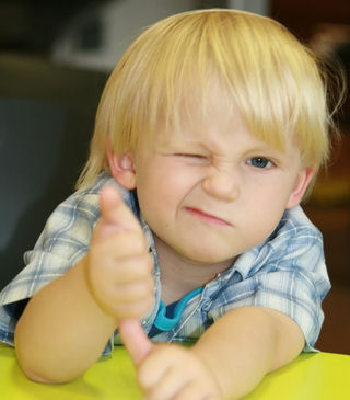 young child giving thumbs up sign