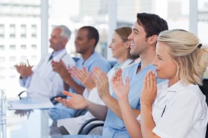 Office team clapping hands during a conference