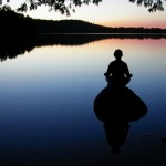 woman meditating on rock on a lake