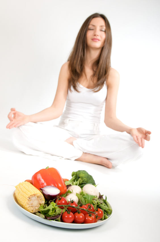 Woman meditating before plate of vegetables