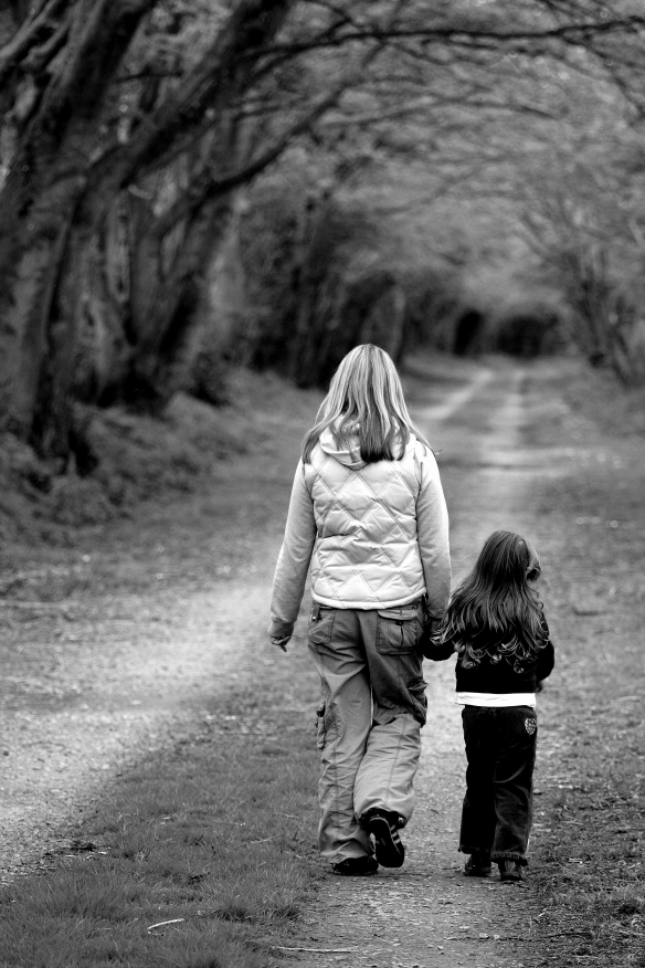 woman walking with young child down path