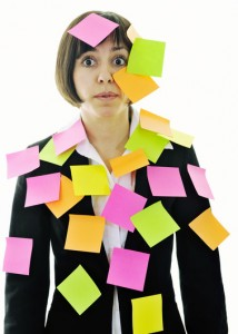 frustrated young business woman with many postits representing concept memory and frustration