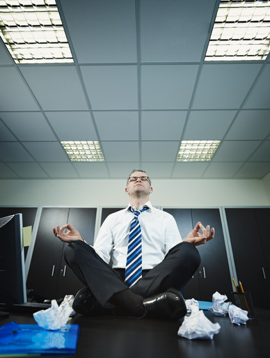 stressed businessman sitting on desk practicing yoga