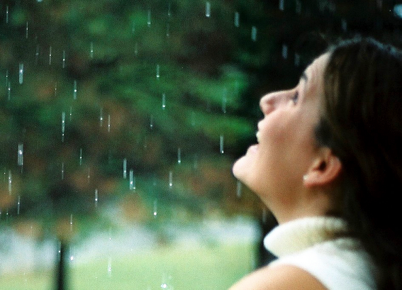 Woman smiling at window while raining outside