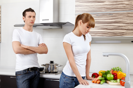 Girl in kitchen with back turned to man