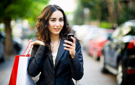 Woman on street with shopping bag and phone